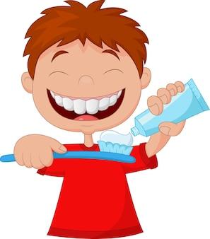 Garoto apertando a pasta de dente em uma escova de dentes