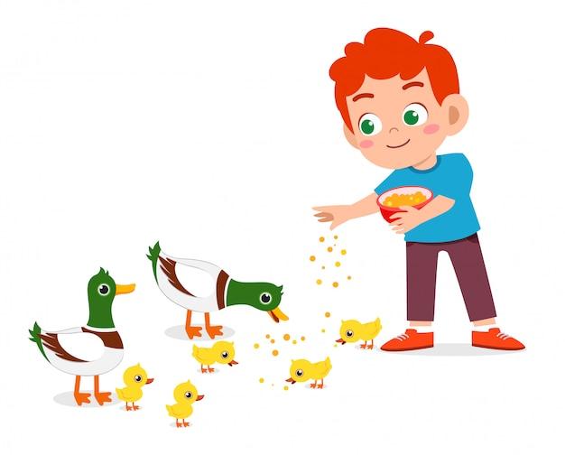 Garoto bonito feliz alimentando pato bonito