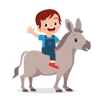 Garoto bonito feliz montando burro bonito