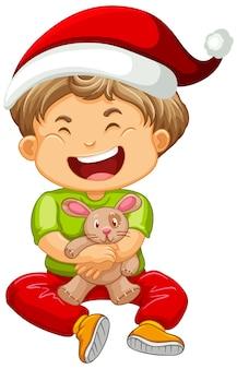 Garoto bonito usando chapéu de natal e brincando com seu brinquedo