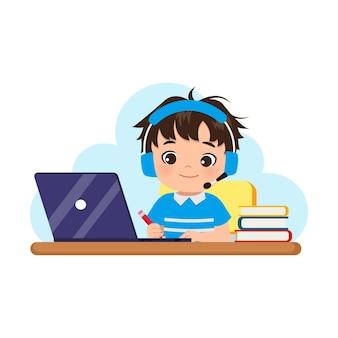 Garoto bonito usando fones de ouvido, aprendendo em casa com seu laptop