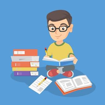 Garoto caucasiano sentada no chão e ler um livro.