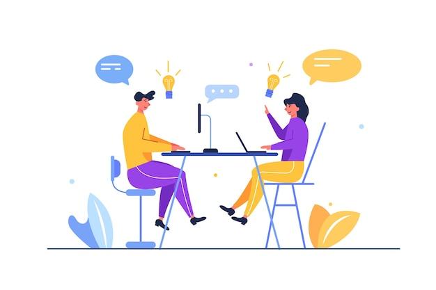 Garoto e garota abrem uma conversa à mesa com um computador e laptop