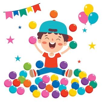 Garoto engraçado brincando com bolas coloridas