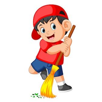 Garoto feliz usando o boné vermelho varrer o lixo com a vassoura longa