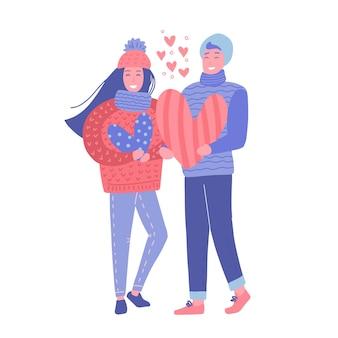 Garoto nad garota segurando grandes corações nas mãos em roupas de inverno. o casal apaixonado do dia de valentne.