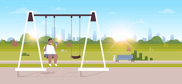 Garoto segurando sorvete sentado no balanço ao ar livre acima do peso cara balançando comendo fast-food