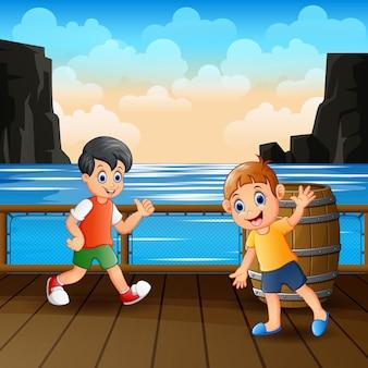 Garotos felizes brincando no porto de madeira