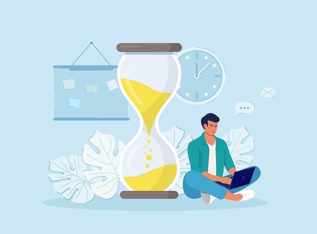 Gerenciamento de tempo. homem trabalhando em um laptop perto do grande relógio de areia