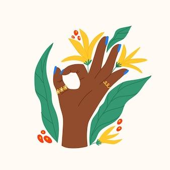 Gesto com flores e folhas composição plana da moda com a mão mostrando sinal de ok
