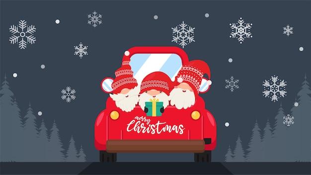 Gnomos anões usando chapéus vermelhos seguram presentes no porta-malas para celebrar o natal no inverno, quando os flocos de neve estão caindo