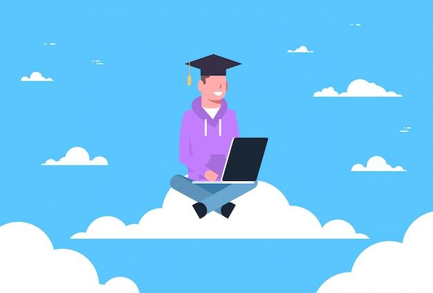 Graduado do estudante do homem novo que senta-se na nuvem com portátil, conceito em linha da tecnologia da educação