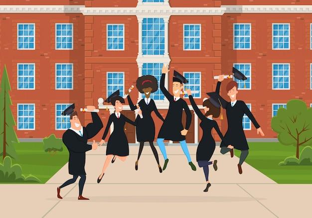Graduados felizes pulam e se alegram no pátio em frente à universidade.