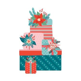 Grande pilha de presentes coloridos com laços é decorada com elementos florais de natal. feliz natal e ano novo. poinsétia, agulhas, flores, folhas, frutos. estilo retro moderno.