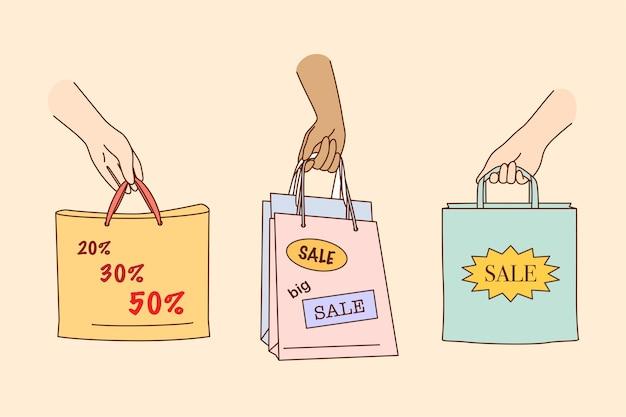 Grande venda, compras, desconto no conceito de lojas. pessoas com as mãos segurando sacolas coloridas de compras ou presentes com porcentagens de desconto