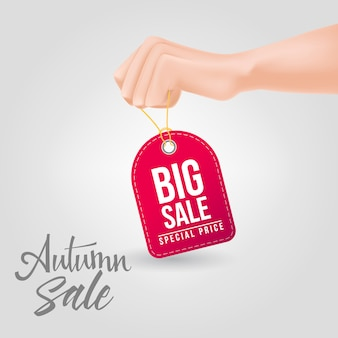 Grande venda, letras de preço especial na tag sendo realizada com a mão
