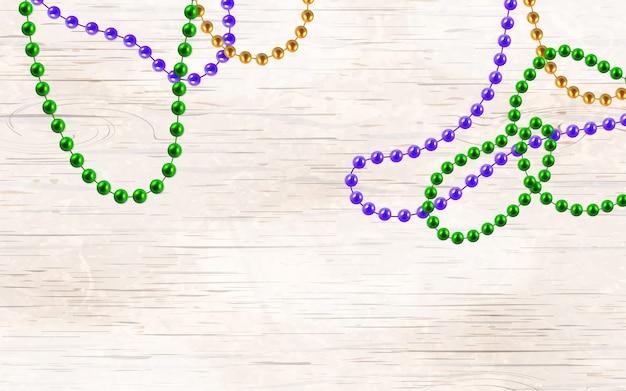 Grânulos de ouro, verdes e roxos multicoloridos 3d isolados em fundo de madeira. decorações de mardi gras.