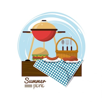 Grelha de carvão e hambúrguer e cesta de piquenique sobre toalha de mesa
