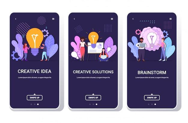 Grupo businesspeople holding brilhante bulbo sucesso teamwork soluções criativas grande idéia brainstorm conceito mistura homens raça homens mulheres colegas de trabalho brainstorming telefone telas coleção comprimento total