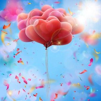 Grupo de balões em forma de coração no céu azul.