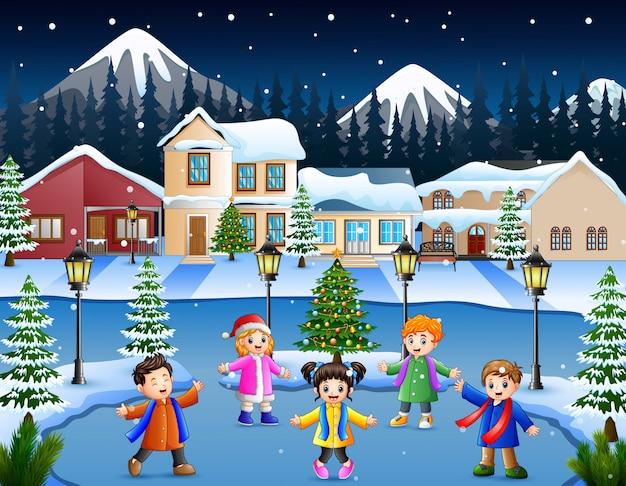 Grupo de criança feliz cantando na aldeia de neve