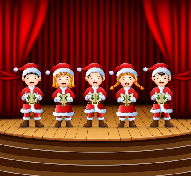 Grupo de crianças cantando canções natalinas no palco