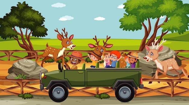 Grupo de crianças no zoológico com muitos veados