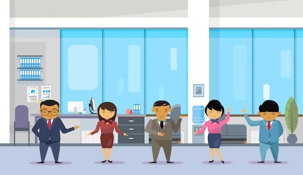 Grupo de empresários asiáticos vestindo ternos no escritório moderno