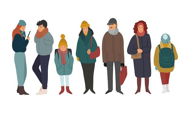 Grupo de homens, mulheres e crianças vestindo roupas de inverno.