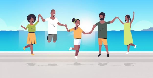 Grupo de jovens pulando na praia homens mulheres de mãos dadas conceito de férias de verão amigos se divertindo à beira-mar mar oceano feriado curso comprimento total horizontal
