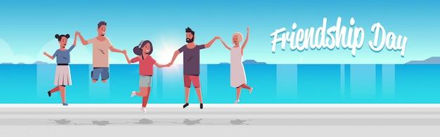 Grupo de jovens pulando na praia homens mulheres de mãos dadas férias de verão amizade dia celebração amigos se divertindo à beira-mar