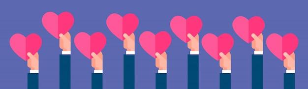 Grupo de mãos segurando o coração rosa forma banner horizontal do conceito de dia dos namorados