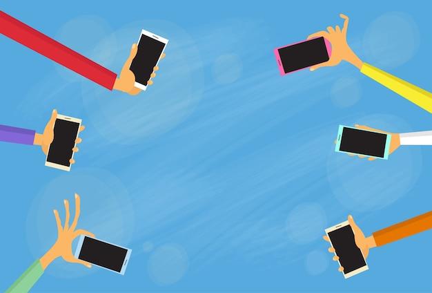Grupo de mãos segure telefones inteligentes coloridos
