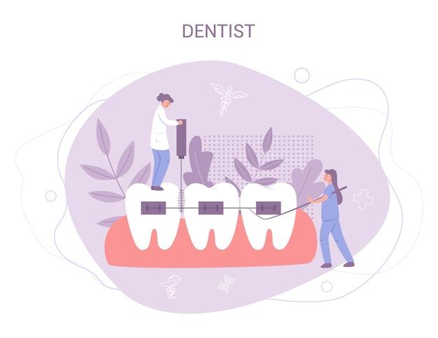 Grupo de pequenos dentistas uniformizados trata dente gigante com equipamento médico