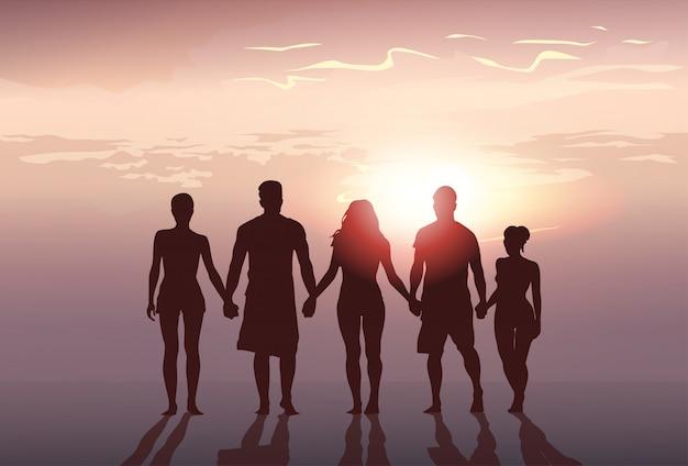 Grupo de pessoas de silhueta fica de mãos dadas homem e mulher de comprimento total sobre fundo por do sol