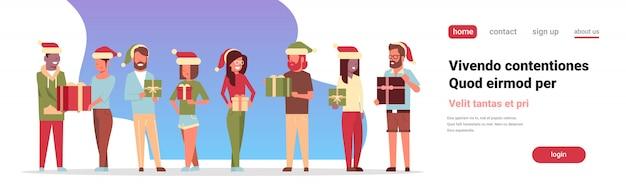 Grupo de pessoas em pé segurando a caixa de presente presente feliz natal feliz ano novo