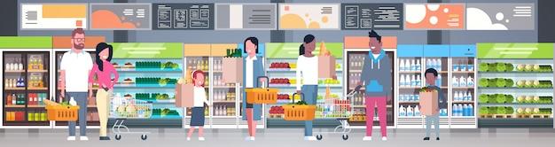 Grupo de pessoas segurando sacos, cestas e empurrando troles no supermercado