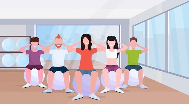Grupo de pessoas sentado na esfera da aptidão homens mulheres fazendo exercícios de imprensa treinamento no ginásio aeróbio lifestyle saudável conceito moderno estúdio de saúde interior estúdio