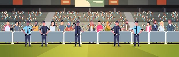 Grupo de policiais de raça mista, controlando a multidão de fãs na arena do estádio de esporte no suporte à segurança do campeonato de partidas de futebol