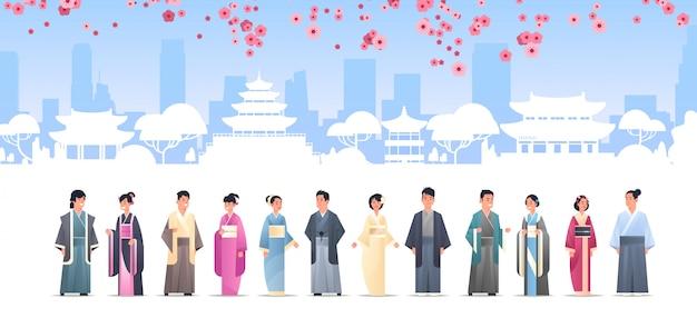 Grupo de povos asiáticos em roupas tradicionais homens mulheres vestindo trajes antigos juntos caracteres chineses ou japoneses sobre paisagem de edifícios de pagode