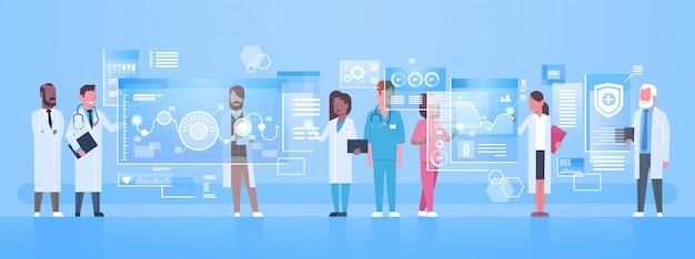 Grupo diverso dos doutores usa a tela de computador virtual com conceito da tecnologia da inovação dos botões de digitas