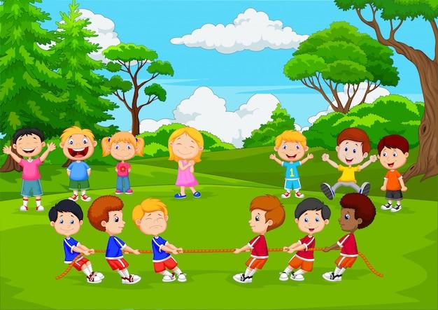 Grupo dos desenhos animados de crianças brincando de cabo de guerra no parque