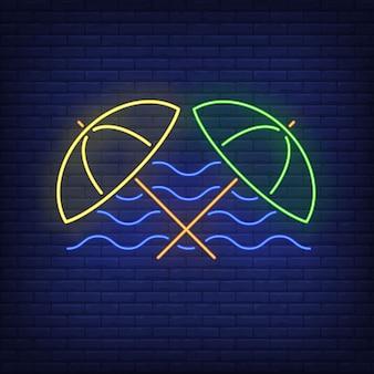 Guarda-chuvas de praia e sinal de néon de ondas do mar. verão, férias, férias, resort.