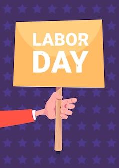 Hand holding placard dia do trabalhador