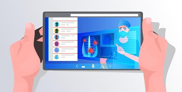 Hans usando tablet com médico mascarado examinando células de coronavírus do sintoma de pneumonia viral por raio-x na tela