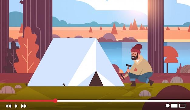 Hiker blogger gravação de vídeo on-line homem vlogger configurar barraca no parque de campismo streaming ao vivo blogging caminhadas conceito paisagem fundo horizontal comprimento total