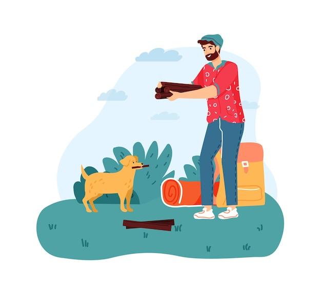Homem acampando, segurando lenha para a fogueira. menino barbudo com cachorro para para fazer fogueira com toras.