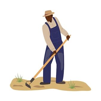 Homem africano de macacão e chapéu de palha trabalhando no campo