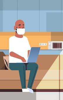 Homem afro-americano em máscara protetora usando laptop conceito de quarentena pandemia de coronavírus trabalhar em casa educação treinamento freelance moderna sala de estar interior comprimento total vertical