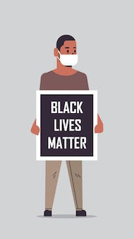 Homem afro-americano mascarado, segurando uma bandeira de vida negra, campanha contra a discriminação racial, apoio à igualdade de direitos